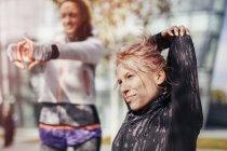 Due corridori donne che allungano le braccia in città — Foto stock