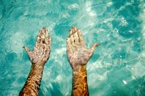 Hands under tropical water — Stock Photo