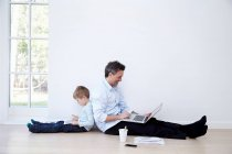 Father and son sitting back to back and using laptop and digital tablet — Stock Photo
