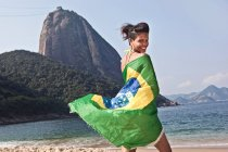 Man on beach with Brazilian flag, Rio de Janeiro, Brazil — Stock Photo