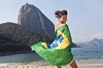 Людина на пляжі з бразильським прапором, Ріо-де-Жанейро, Бразилія — стокове фото