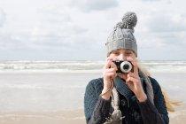Женщина у моря с камерой — стоковое фото