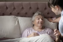 Personal care assistant chatting to senior woman in bed — Stock Photo