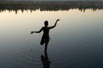 Woman in yoga pose in lake — Stock Photo