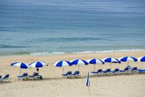 Parasols et transats sur la plage — Photo de stock