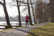 Woman nordic walking on tree lined path by pond — Stock Photo