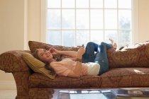 Дівчинка-підліток лежить на дивані з навушники — стокове фото