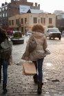 Vista posteriore della donna con shopping bag sulla strada della città — Foto stock