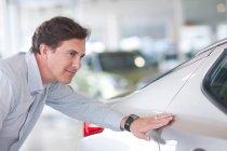 Porträt eines Mannes, der sein Auto im Verkaufsraum untersucht — Stockfoto