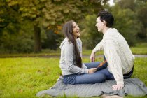 Young couple on blanket in park, laughing — Stock Photo