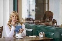 Reife Frau mit Smartphone zum Lippenstift am Bürgersteig Café-Tisch anwenden — Stockfoto