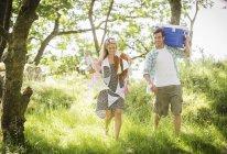 Junges Paar im Wald mit Girlanden und Kühlbox — Stockfoto