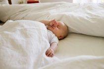 Baby girl asleep on bed — Stock Photo