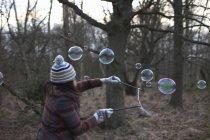 Donna nella foresta utilizzando bacchette di bolla per fare bolle — Foto stock