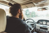Over shoulder view of bearded man driving a car — Stock Photo