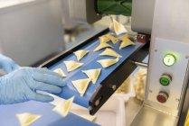 Рабочие руки сортируют равиоли на макаронном заводе — стоковое фото