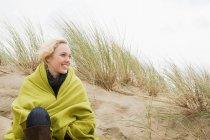 Женщина на побережье в одеяле — стоковое фото