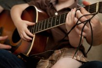 Cropped image of Boy and father playing guitar — Stock Photo