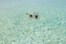Meados casal adulto snorkeling e olhar para o peixe — Fotografia de Stock