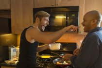 Male couple in kitchen, fooling around, making breakfast — Stock Photo