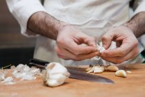 Mani del cuoco unico maschio pelatura aglio — Foto stock