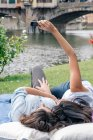 Lesbian couple lying down using smartphone to take selfie in front of Ponte Vecchio over river Arno, Florence, Tuscany, Italy — Stock Photo