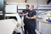 Arbeiter überprüfen Schalttafel in Maschinenfabrik — Stockfoto