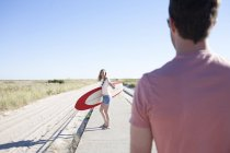 Couple with surfboard on coastal path, Breezy Point, Queens, New York, USA — Stock Photo