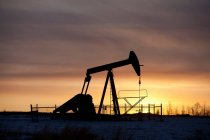 Silhouette of oil well at sunset — Stock Photo
