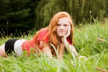 Teenage girl lying down on the grass chilling out — Stock Photo