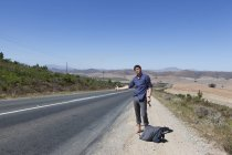 Hitchhiker on side of road — Stock Photo