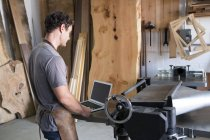 Carpenter at his workshop, using laptop — Stock Photo