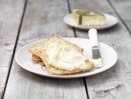 Triangoli di formaggio morbido spalmati su crackers quadrati con coltello del burro sulla piastra — Foto stock