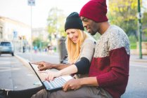 Coppia utilizzando computer portatile sul marciapiede all'aperto durante il giorno — Foto stock