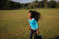 Souriante fille courir dans le champ — Photo de stock