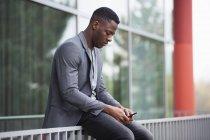 Jovem empresário sentado sobre trilhos, usando smartphone — Fotografia de Stock