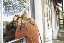 Mujer mirando por la ventana del edificio, Londres, Reino Unido - foto de stock