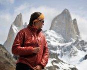 Mujer volando su chaqueta frente a Monte Fitz Roy en el Parque Nacional Los Glaciares, El Chaltén, Argentina - foto de stock