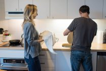 Mid adult couple washing plate at kitchen sink — Stock Photo