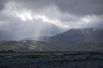 Vue de paysage des montagnes sous un ciel nuageux avec des rayons de soleil — Photo de stock