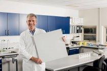 Ученый-мужчина с чистым знаком в лаборатории — стоковое фото