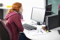 Junge Studentin am Schreibtisch liest Computer — Stockfoto