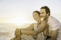 Mid adult couple sitting on beach at sunset, Cape Town, South Africa — Stock Photo