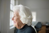 Ritratto della donna maggiore che osserva dalla finestra — Foto stock