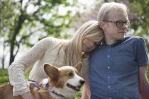 Young couple sitting in park with corgi dog — Stock Photo
