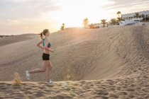 Full length side view of mid adult woman running across sand dune — Stock Photo