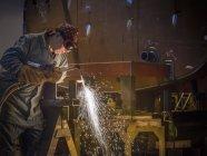 Welder using oxyacetylene torch to cut steel in factory — Stock Photo