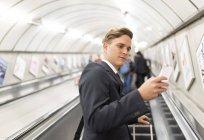 Businessman texting on escalator, London Underground, UK — Stock Photo