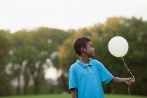 Boy at birthday party holding balloon — Stock Photo