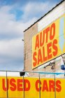 Auto sales and used cars signs on blue cloudy sky — Stock Photo